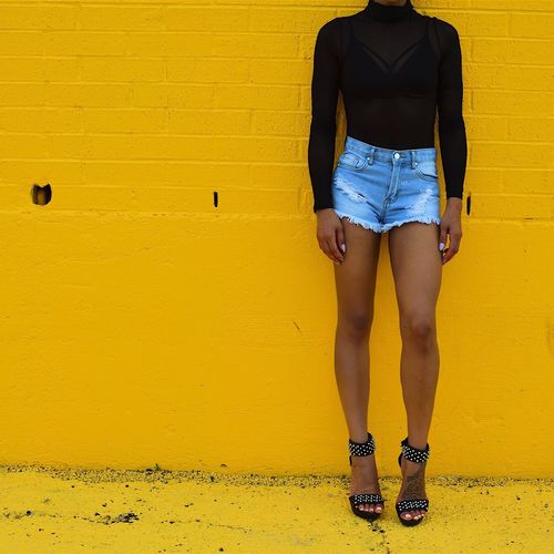 Low Section Of Woman In Hot Pants Leaning On Yellow Wall