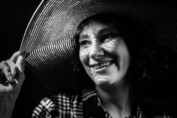 Close-up of smiling woman standing in darkroom