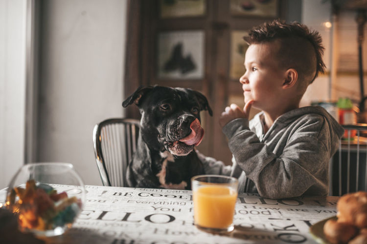 Man and dog sitting on table