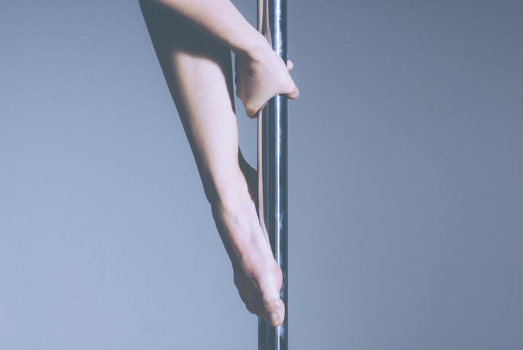 Midsection Of Pole Dancer Against Gray Background