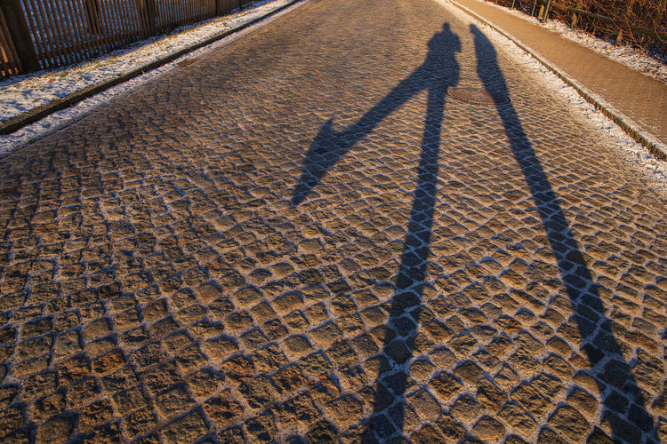 shadow of two guys Shadow Nature Transportation Direction Day Sunlight Outdoors Road Focus On Shadow Men Long Shadow - Shadow Two People Street High Angle View City Cobblestone Footpath Pattern People Real People Group Of People Architecture Paving Stone