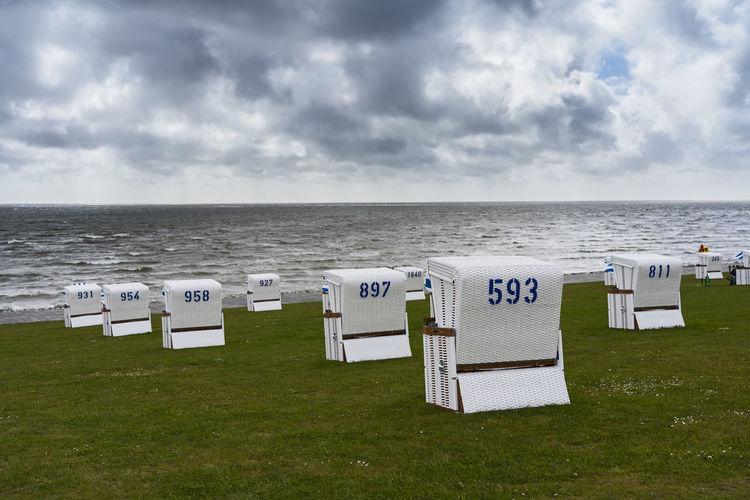 Hooded chairs on beach against sky