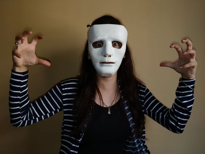 Close-up portrait of shocked woman wearing mask while gesturing against wall