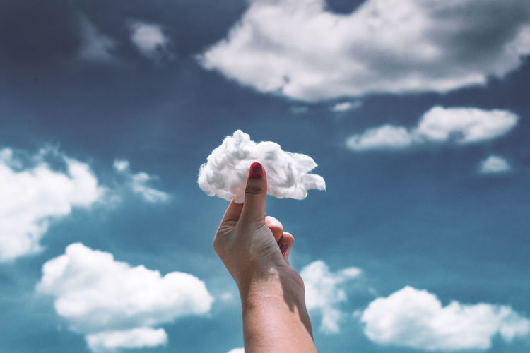 Cropped hand of woman holding cotton against cloudy sky