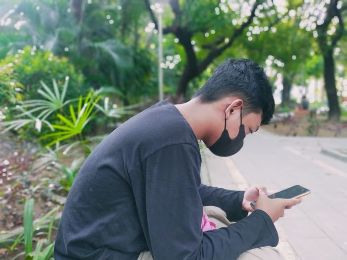 Side view of man using mobile phone outdoors