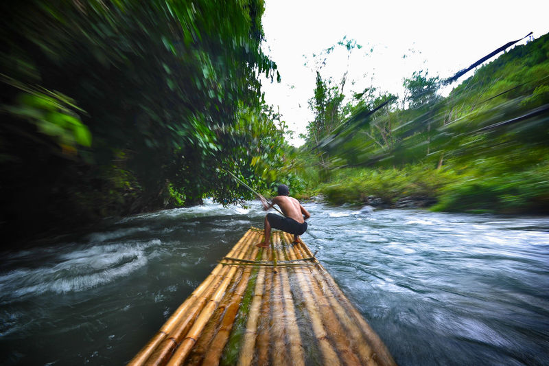 Rear view of man sailing wooden raft in river