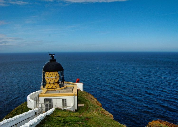 Lighthouse by sea against sky at st abbs