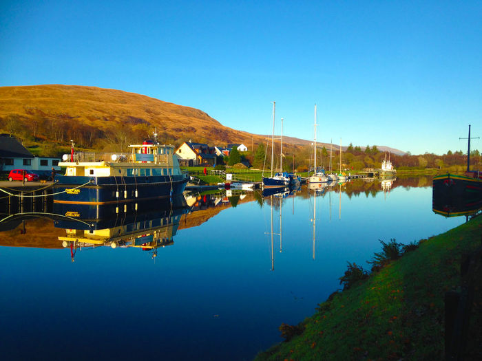 Beauty In Nature Blue Caledonian Canal Canal Canals And Waterways Clear Sky Moored Mountain Nautical Vessel No People Reflection Tranquil Scene Tranquility Water Waterfront