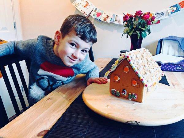 Ginger Christmas Table Indoors  One Person Childhood Real People Looking At Camera Boys Portrait Food Sitting Smiling Creativity Christmas Decoration Gingerbread House Proud Christmas Time Christmas Holidays Festive Season Christmas Jumper Holiday Moments
