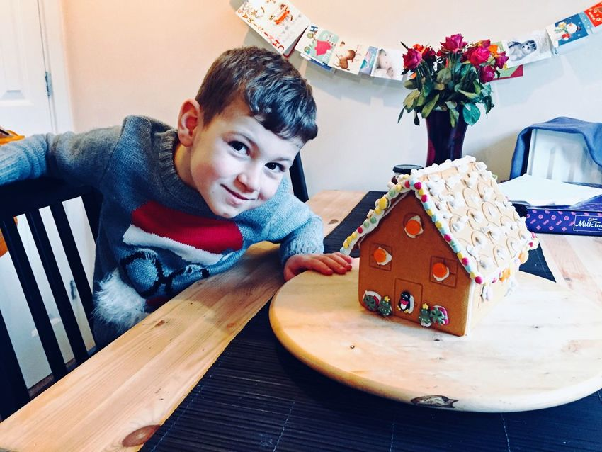 Ginger Christmas Table Indoors  One Person Childhood Real People Looking At Camera Boys Portrait Food Sitting Smiling Creativity Christmas Decoration Gingerbread House Proud Christmas Time Christmas Holidays Festive Season Christmas Jumper