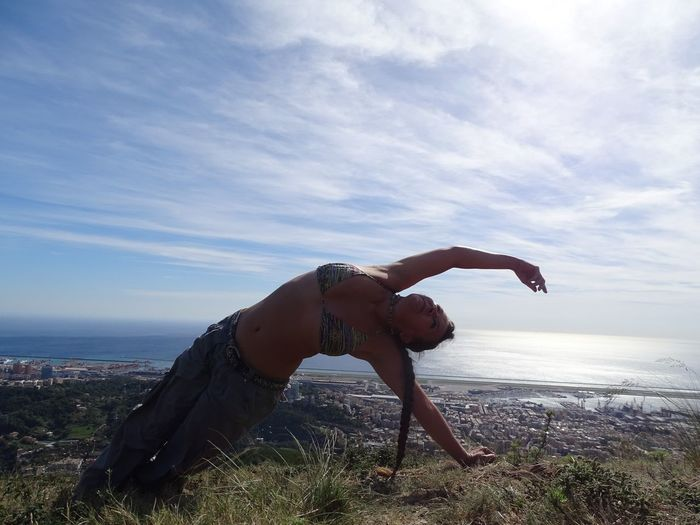 Flexible woman stretching against sky