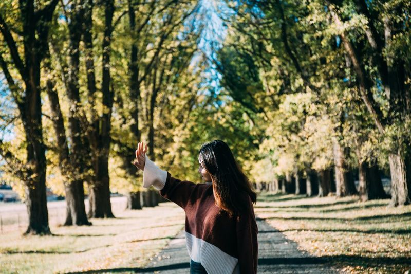 Woman showing stop gesture while standing at park