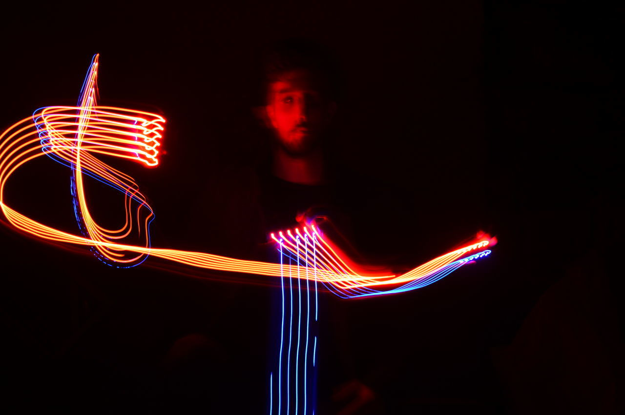 BLURRED MOTION OF MAN AT ILLUMINATED LIGHT TRAILS