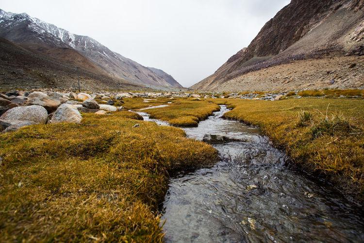 Stream flowing through rocks in river against sky