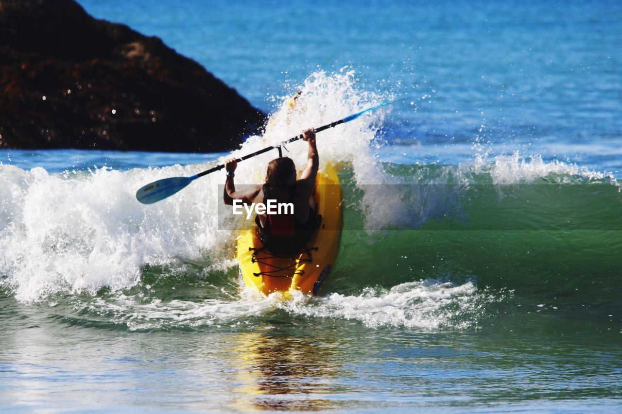 Rear View Of Person Kayaking In Sea