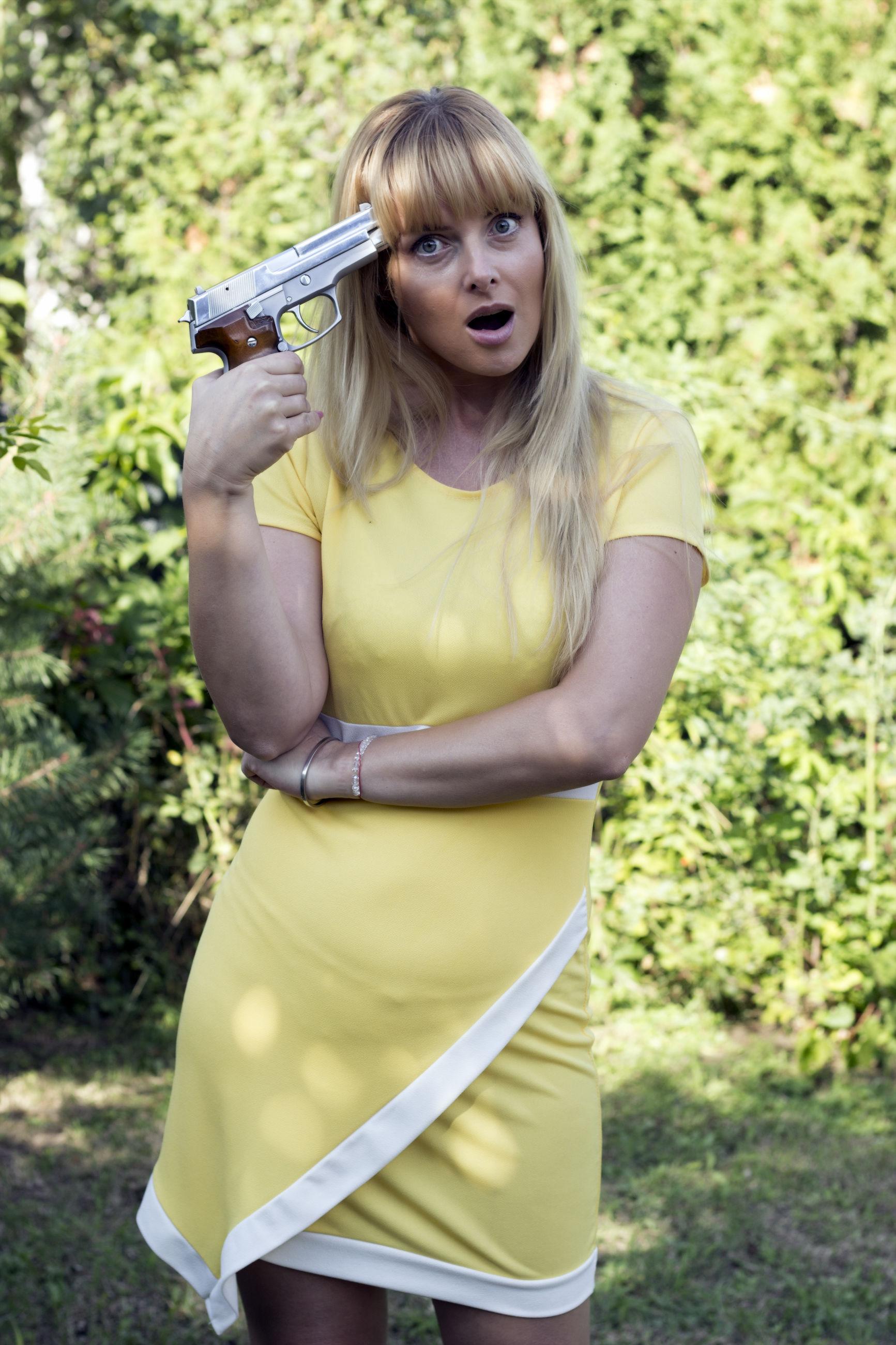 Portrait of woman shooting herself with handgun