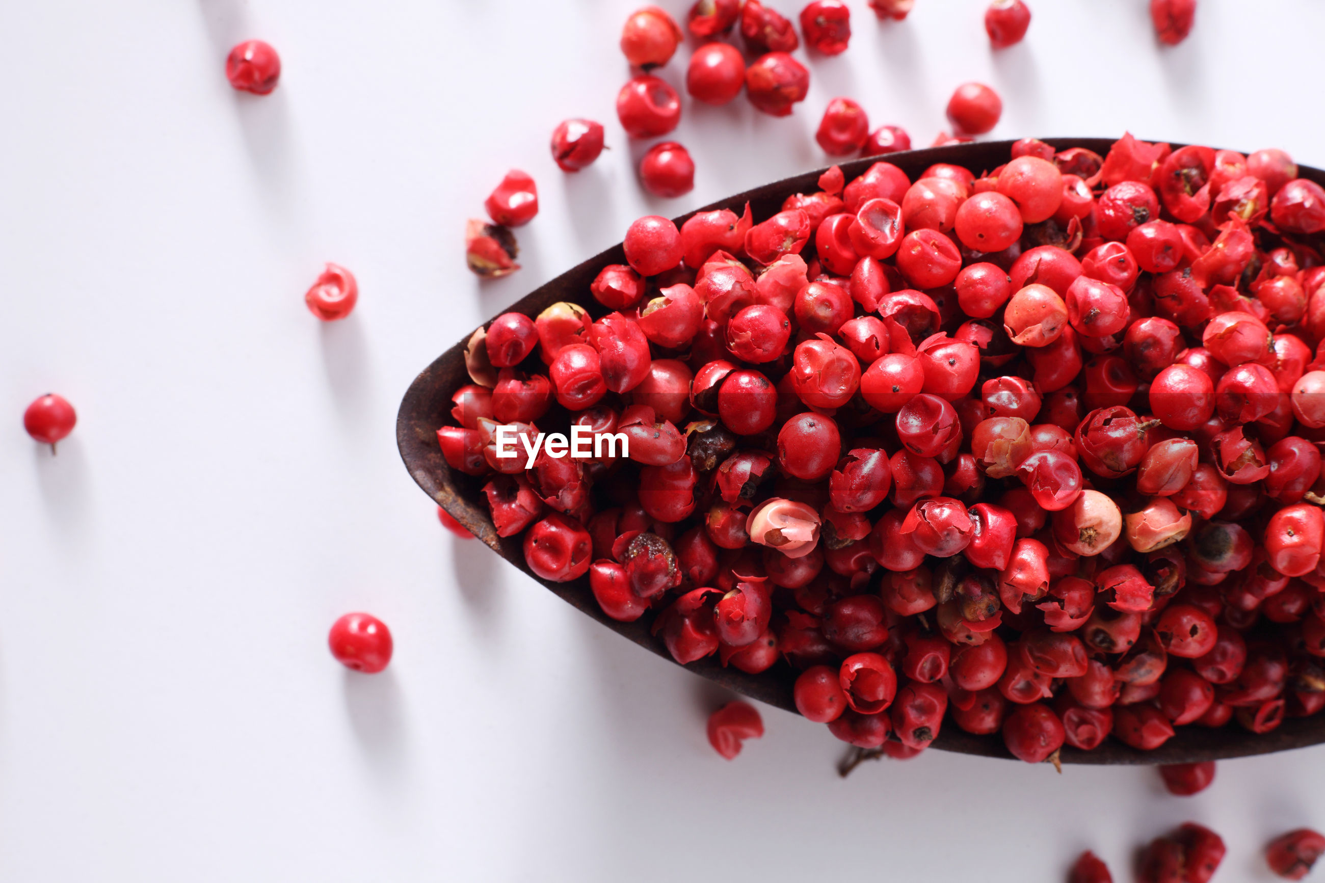 Close-up of red fruits in bowl on white background