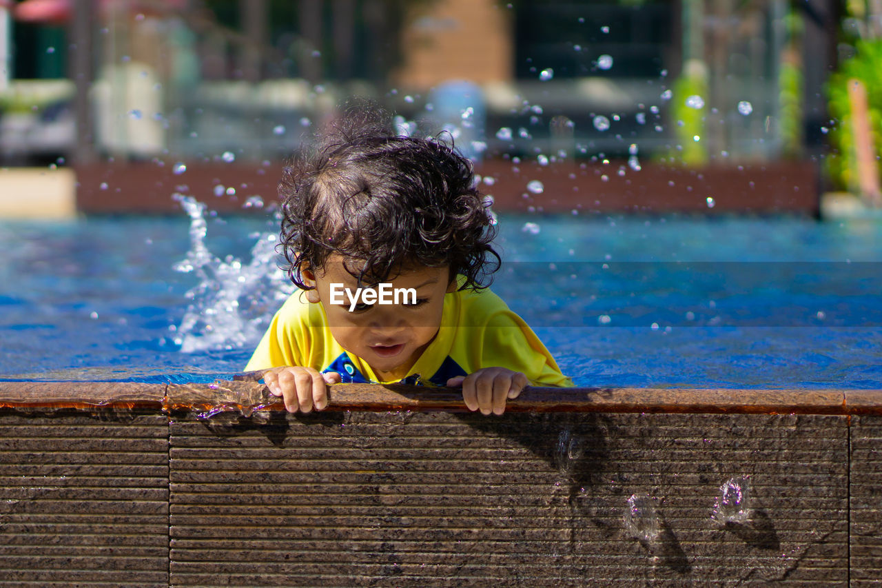 Boy Looking Away While Swimming In Pool