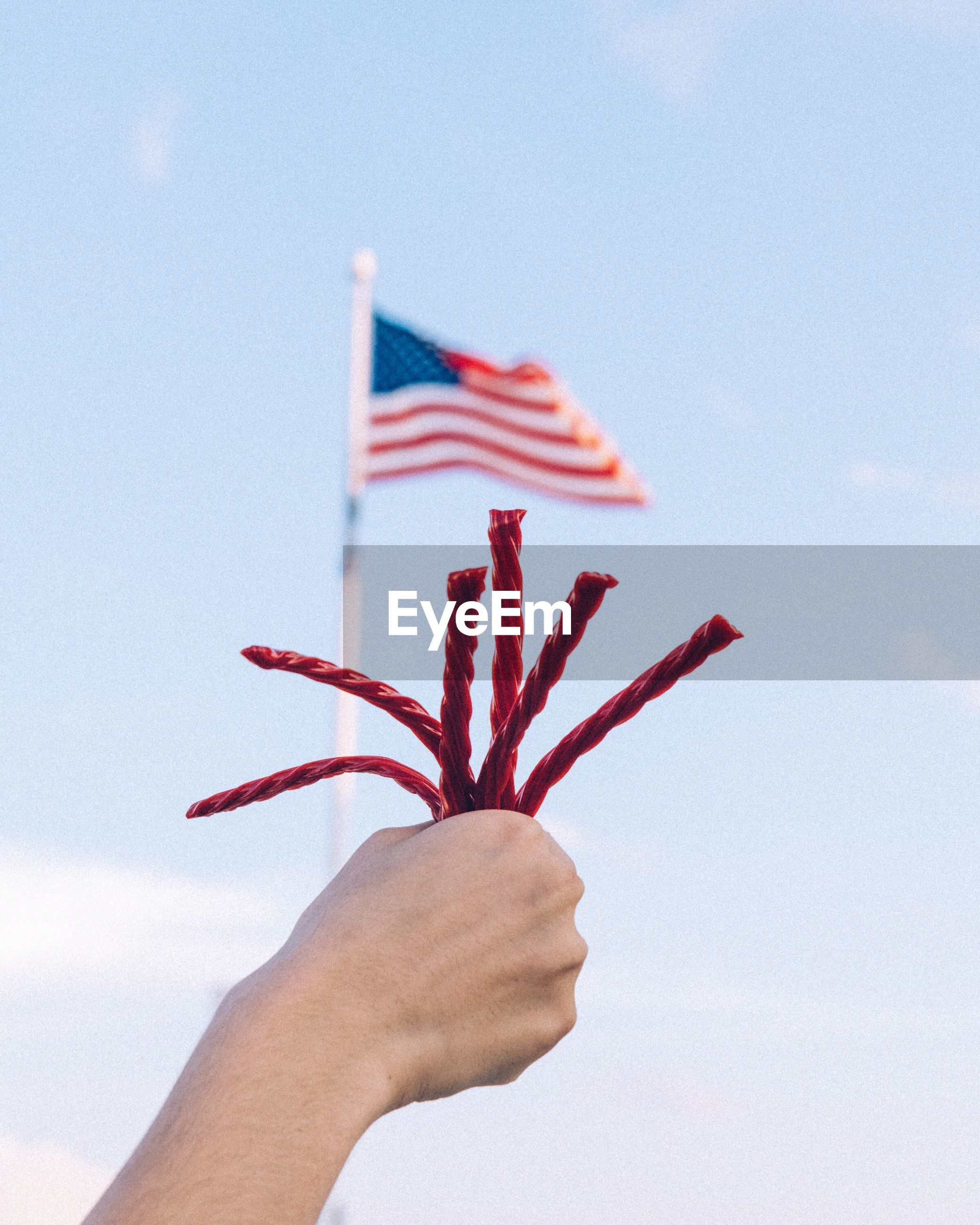 Cropped hand holding string against american flag