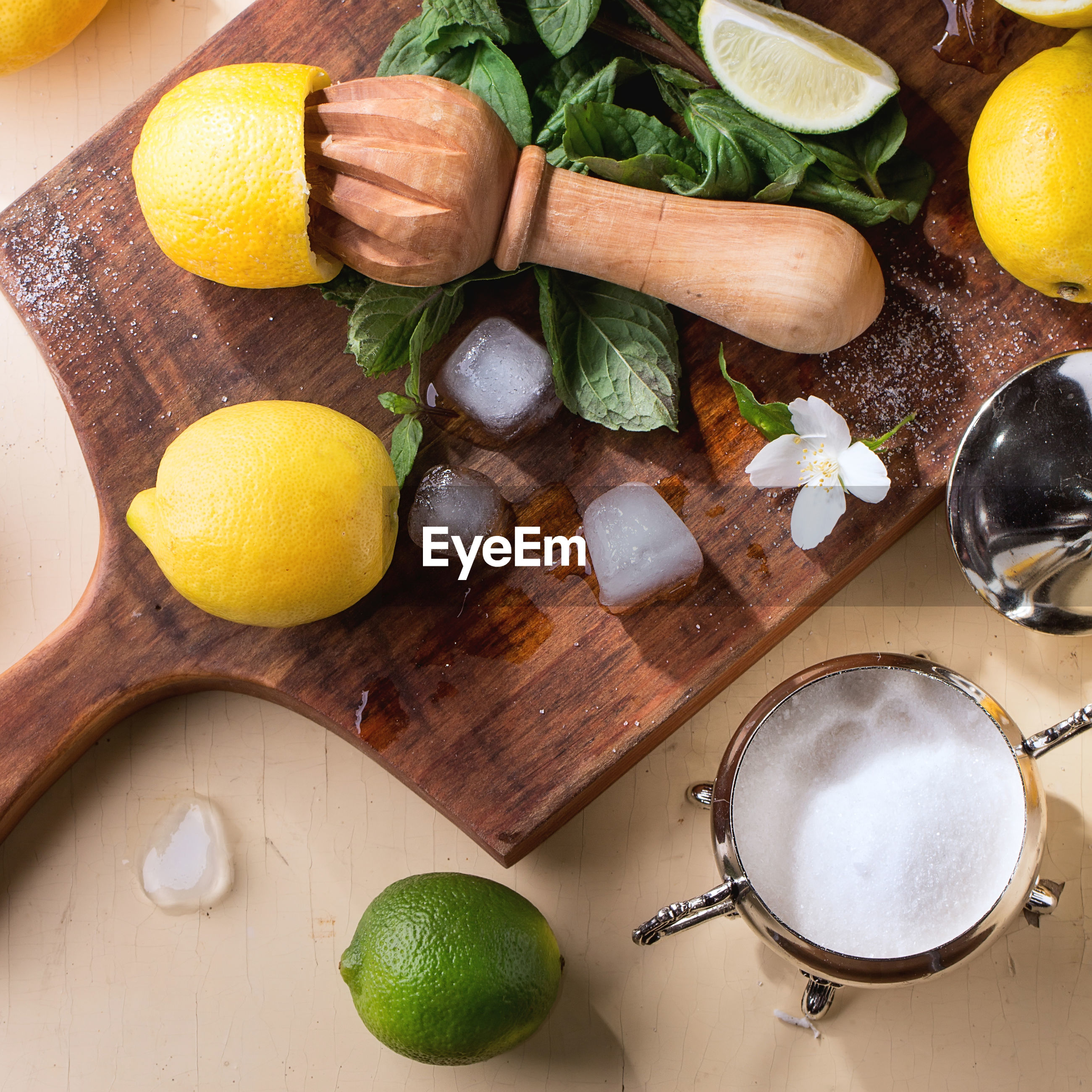High angle view of lemonade ingredients and citrus reamer on table