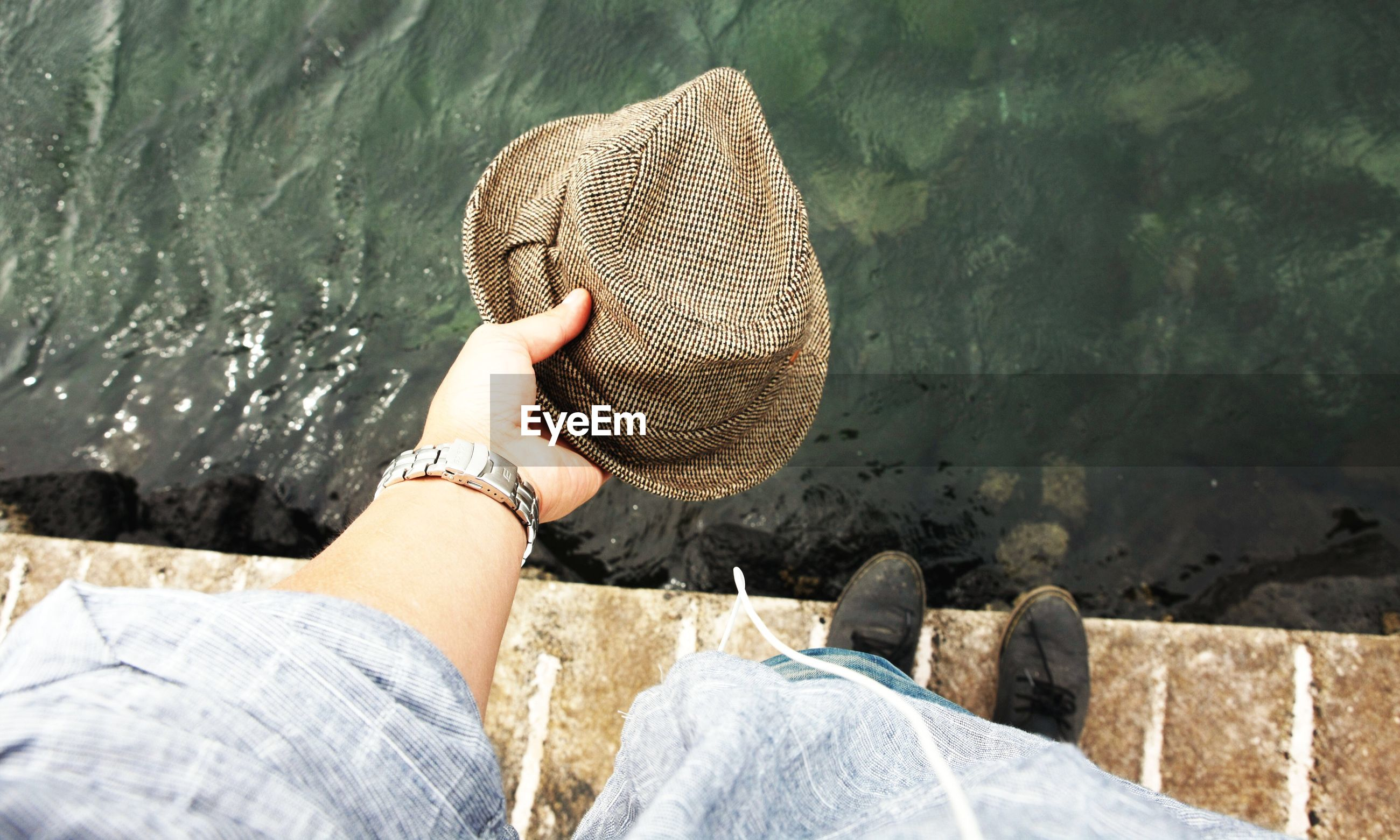 Low section of a man holding hat against water