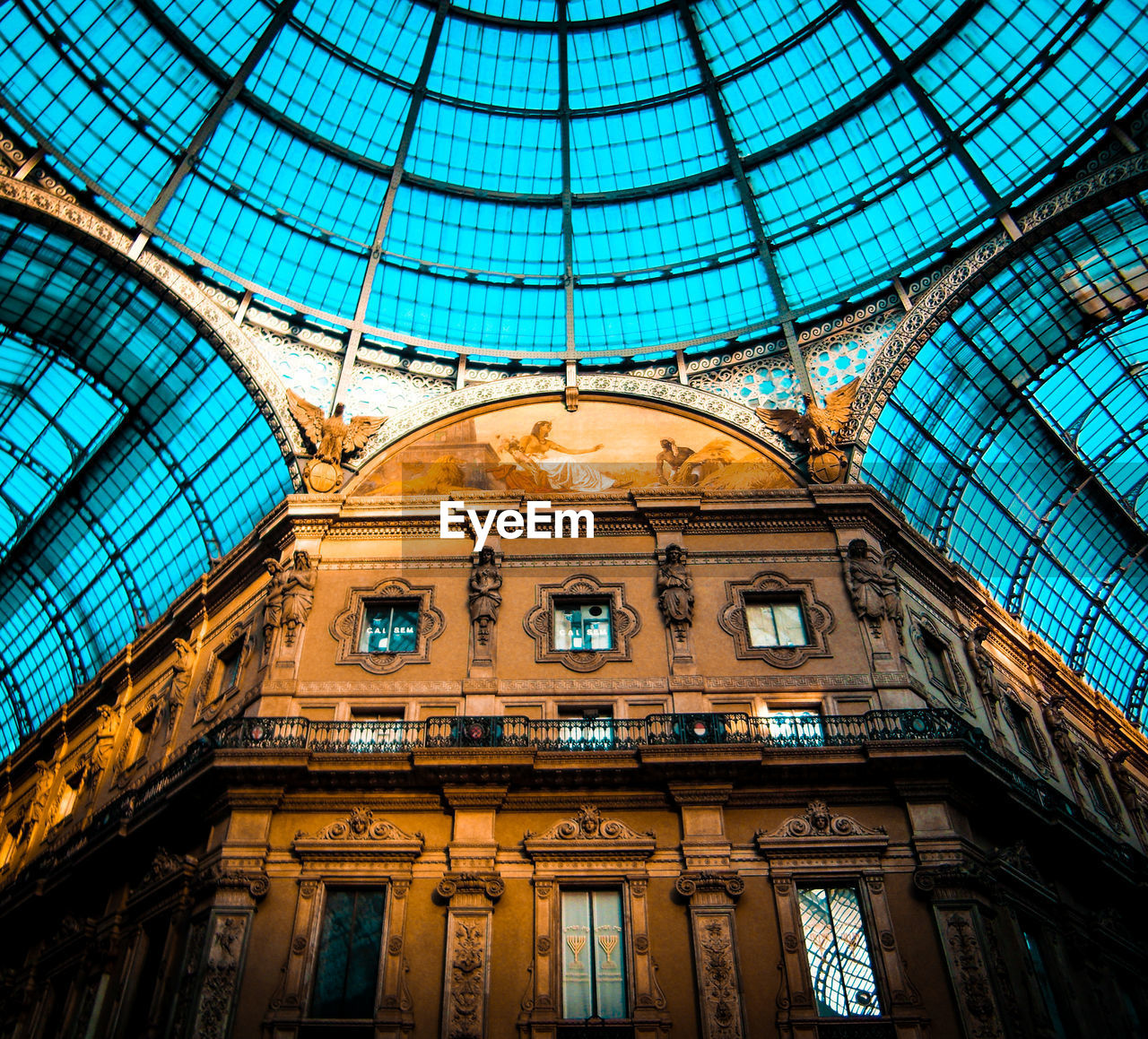 built structure, architecture, low angle view, glass - material, indoors, ceiling, travel destinations, no people, art and craft, window, dome, pattern, history, the past, travel, architectural feature, modern, shopping mall, day, glass, ornate, architecture and art