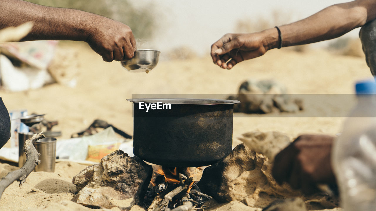 Cropped hands of hikers making tea at jaisalmer desert