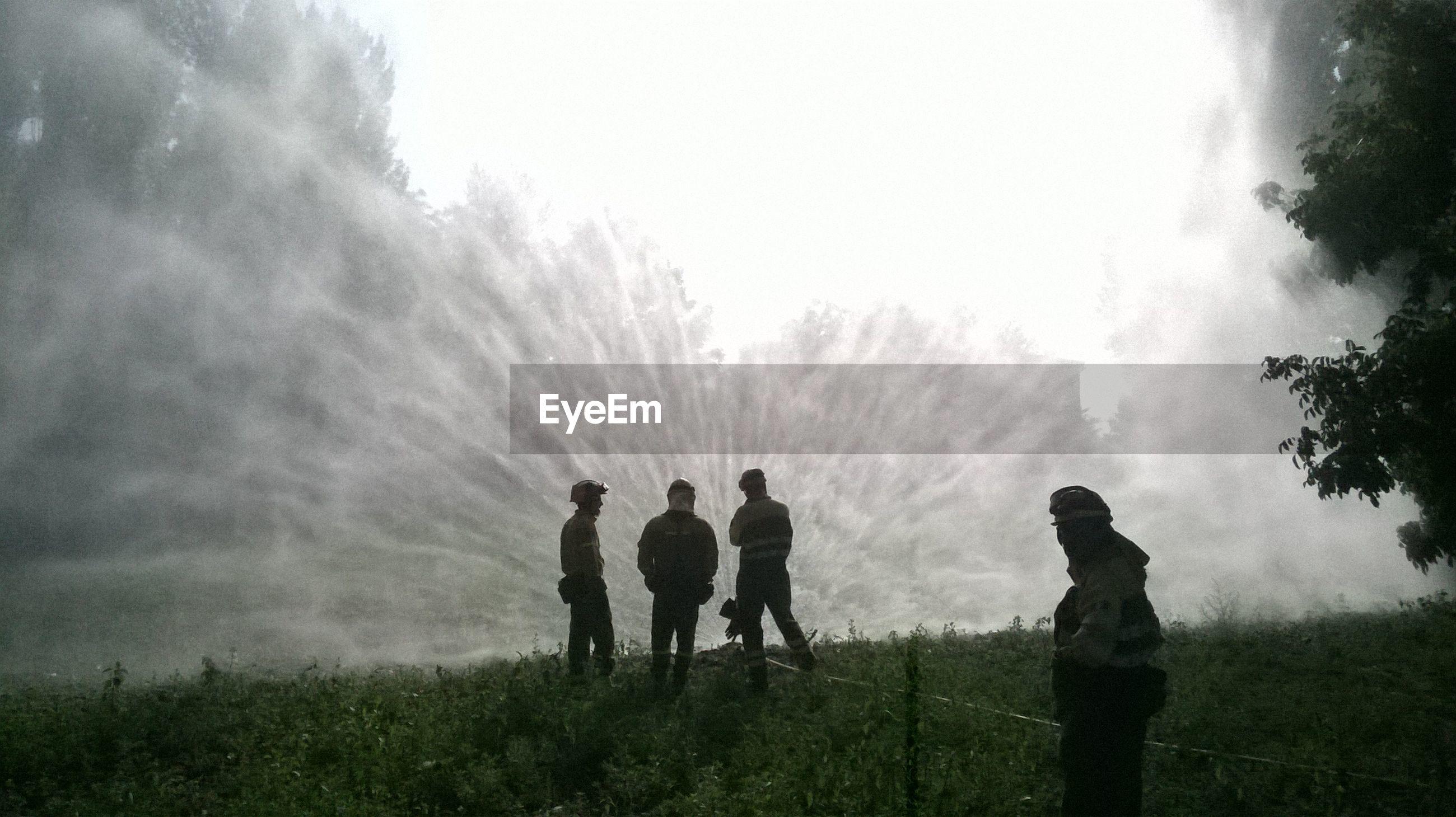 Firefighters on field against sky