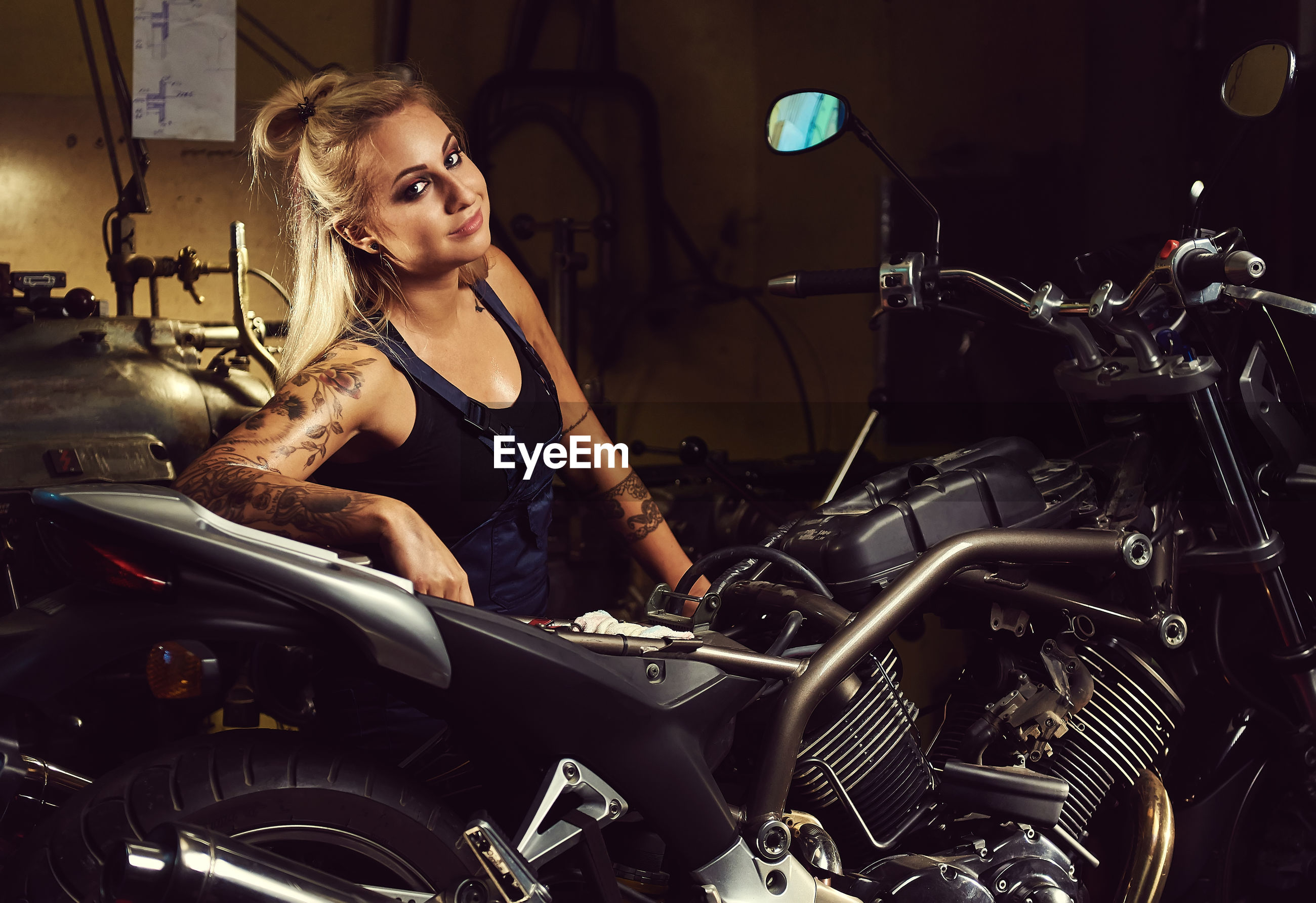 Portrait of young woman sitting by motorcycle at workshop