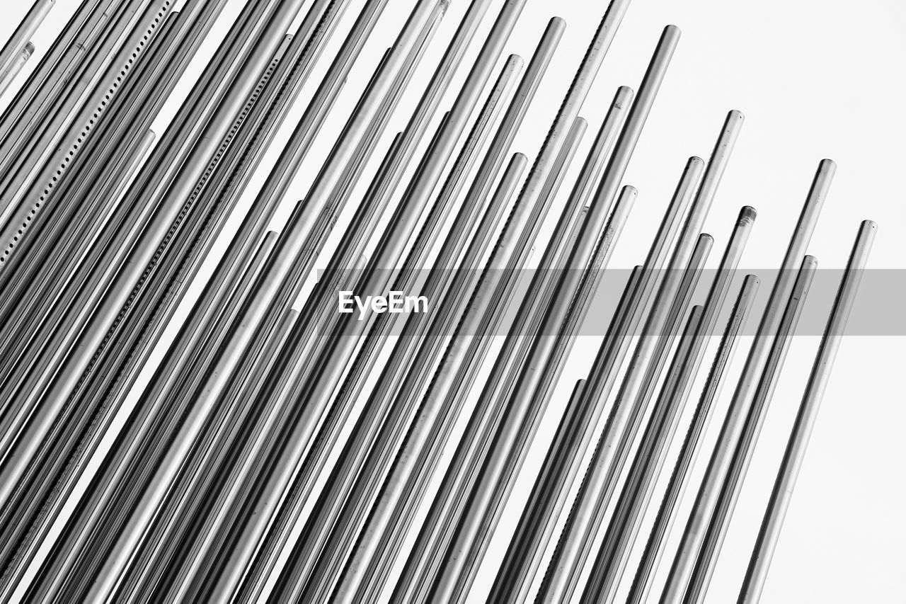 Low angle view of rebars against white background