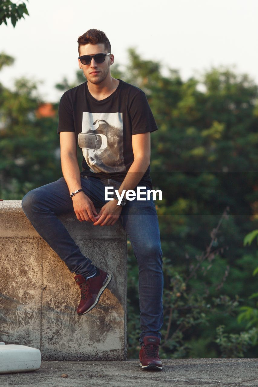 fashion, one person, sunglasses, glasses, young adult, casual clothing, real people, full length, front view, young men, lifestyles, leisure activity, day, focus on foreground, sitting, portrait, nature, cool attitude, outdoors, jeans