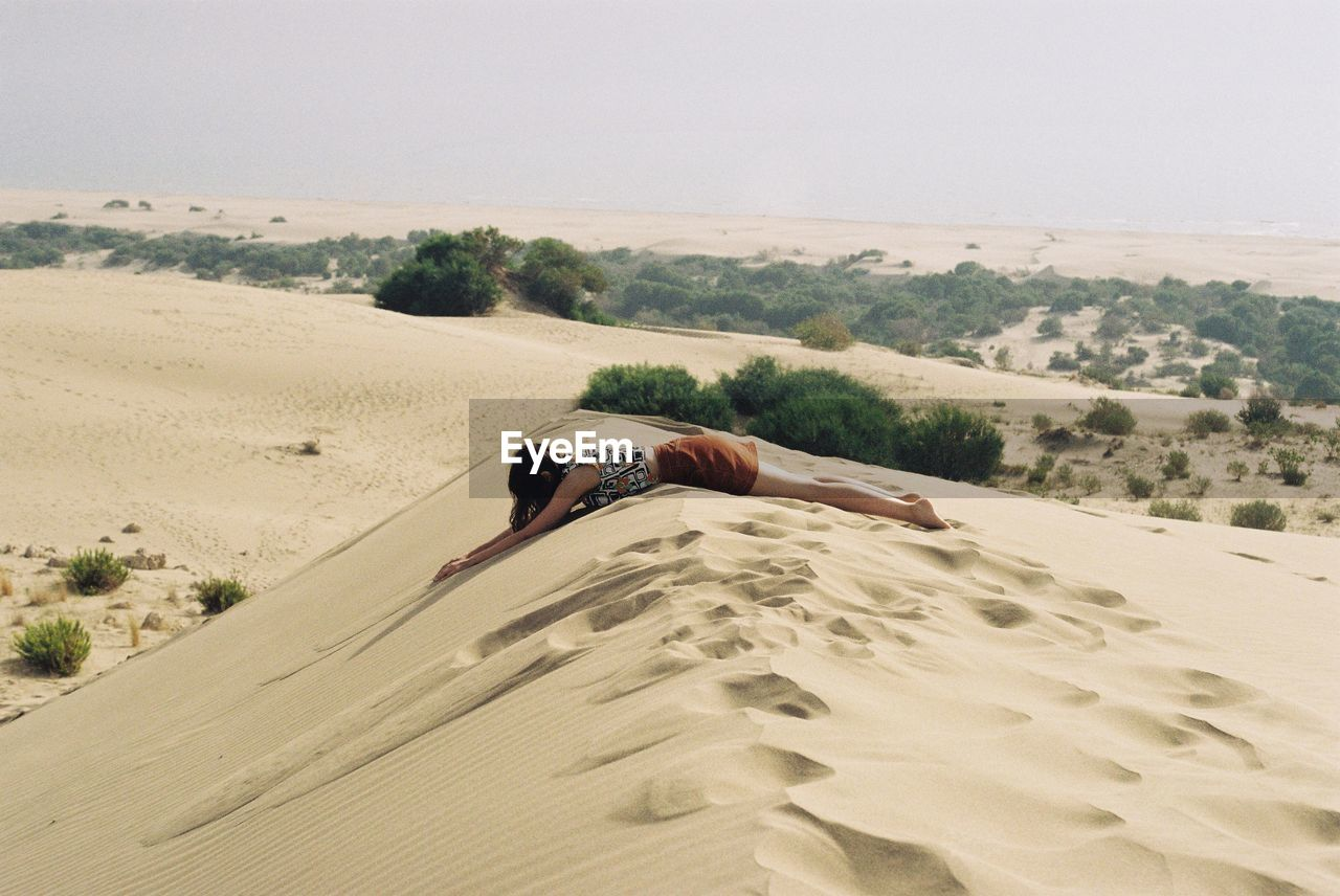 land, sand, one person, leisure activity, landscape, nature, sky, scenics - nature, real people, sand dune, desert, lifestyles, environment, tranquility, holiday, tranquil scene, lying down, beauty in nature, relaxation, arid climate, outdoors, climate