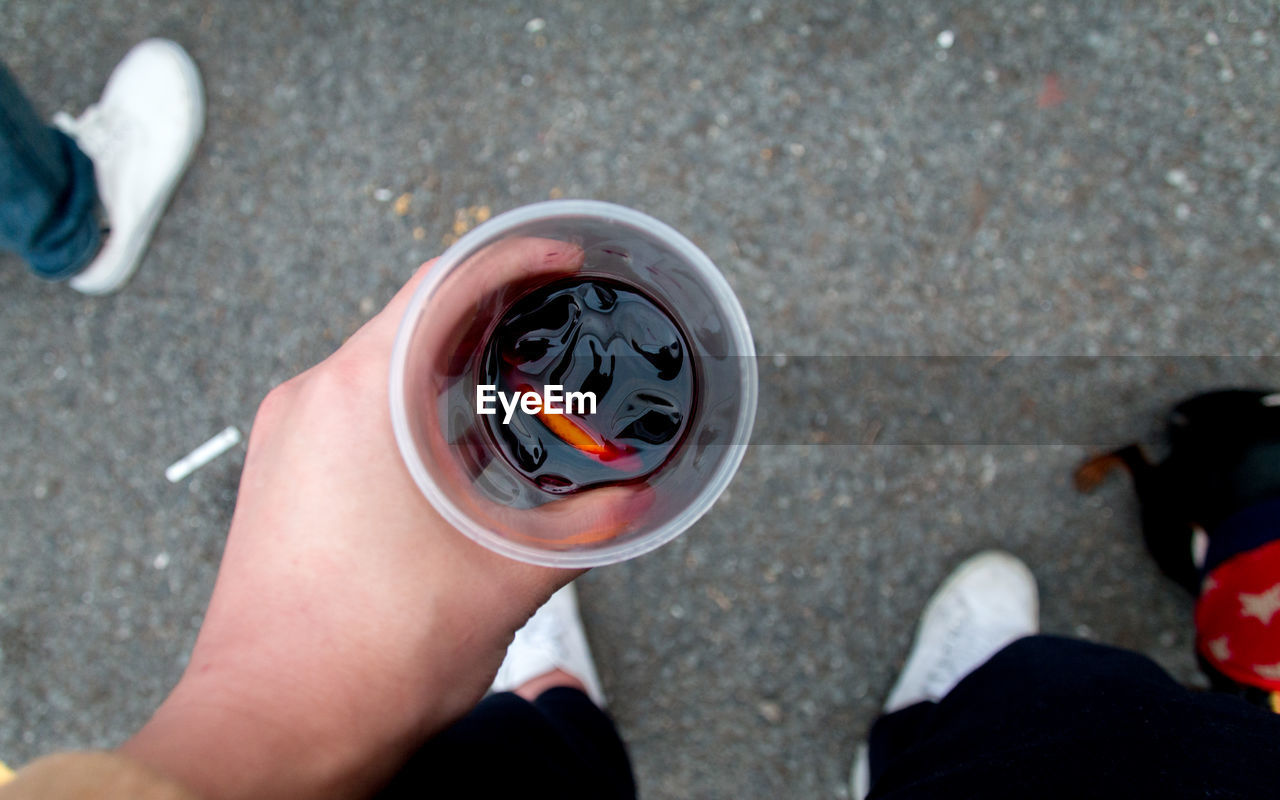 Low Section Of Person Holding Drink On Street