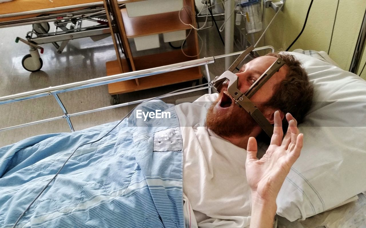 High Angle View Of Patient Shouting With Equipment On Face Lying At Hospital
