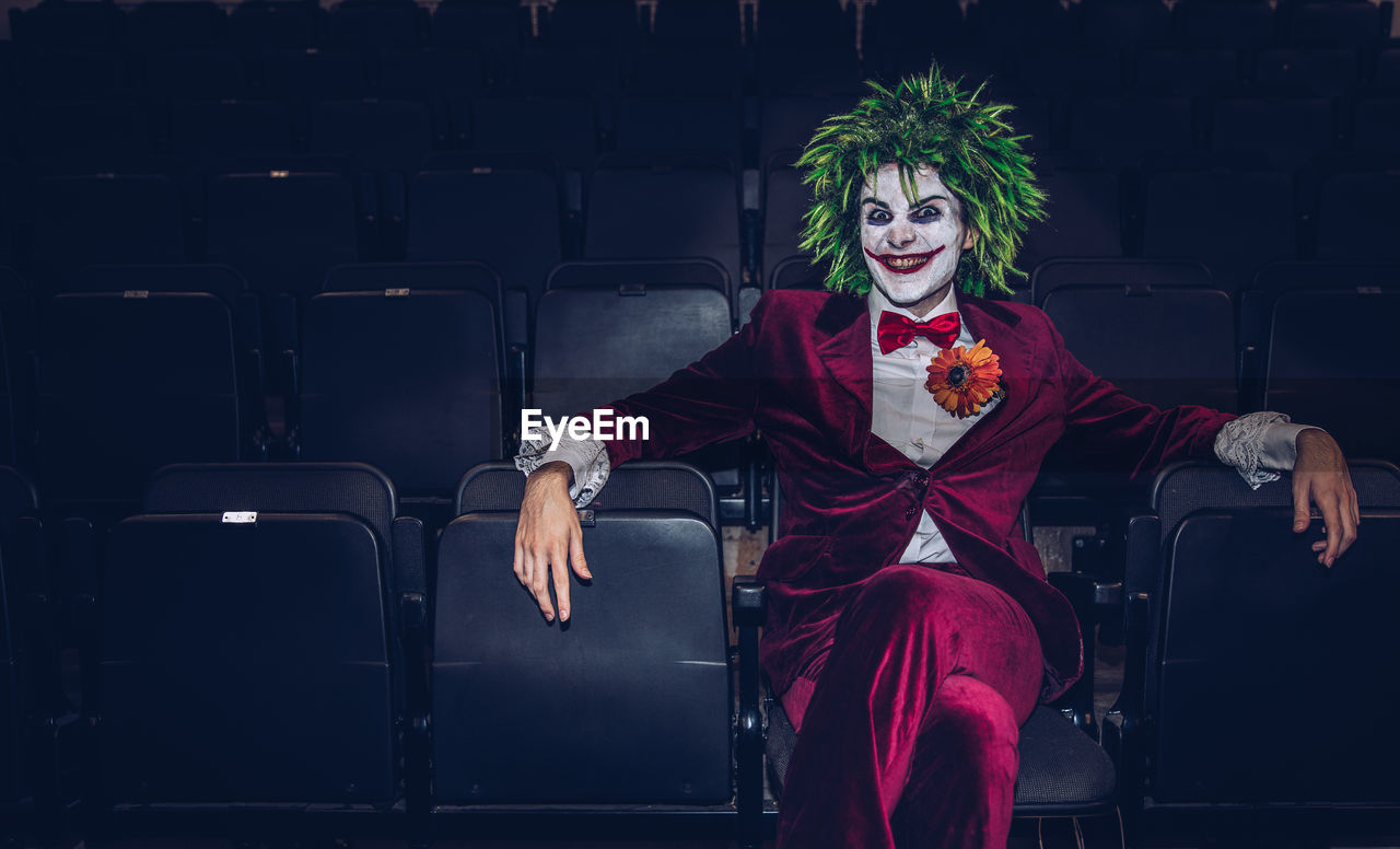 Portrait of man wearing clown costume sitting on chair