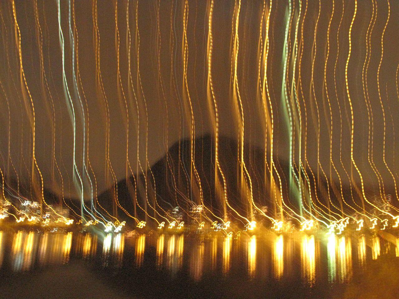 illuminated, water, reflection, no people, pattern, night, nature, waterfront, beauty in nature, scenics - nature, motion, glowing, outdoors, long exposure, light - natural phenomenon, hanging, architecture, idyllic, yellow
