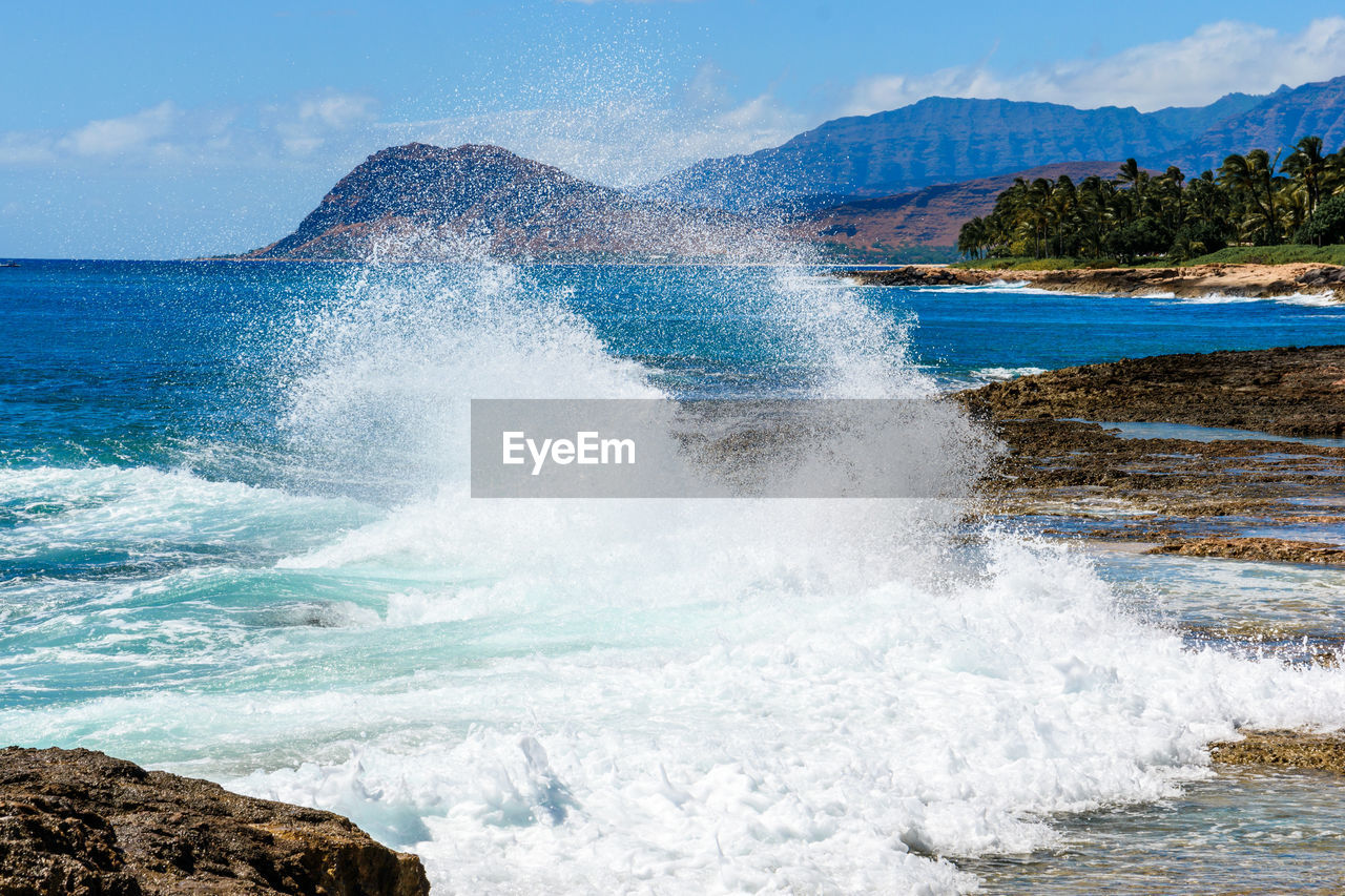 water, sea, sky, beauty in nature, rock, motion, power in nature, wave, splashing, day, rock - object, nature, solid, power, sport, scenics - nature, beach, hitting, no people, breaking, crash, outdoors