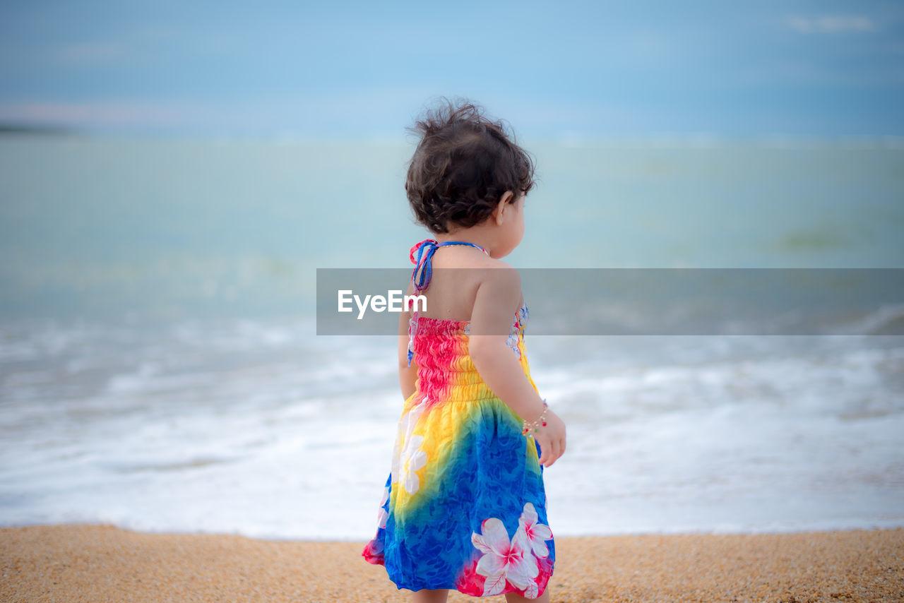 GIRL STANDING AT BEACH