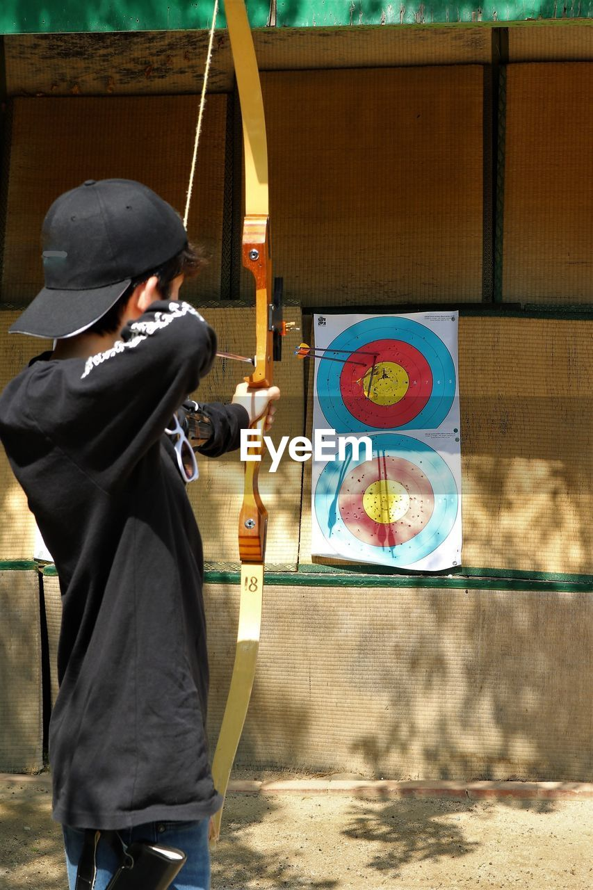 Side View Of Teenage Boy Aiming Sports Target With Arrow