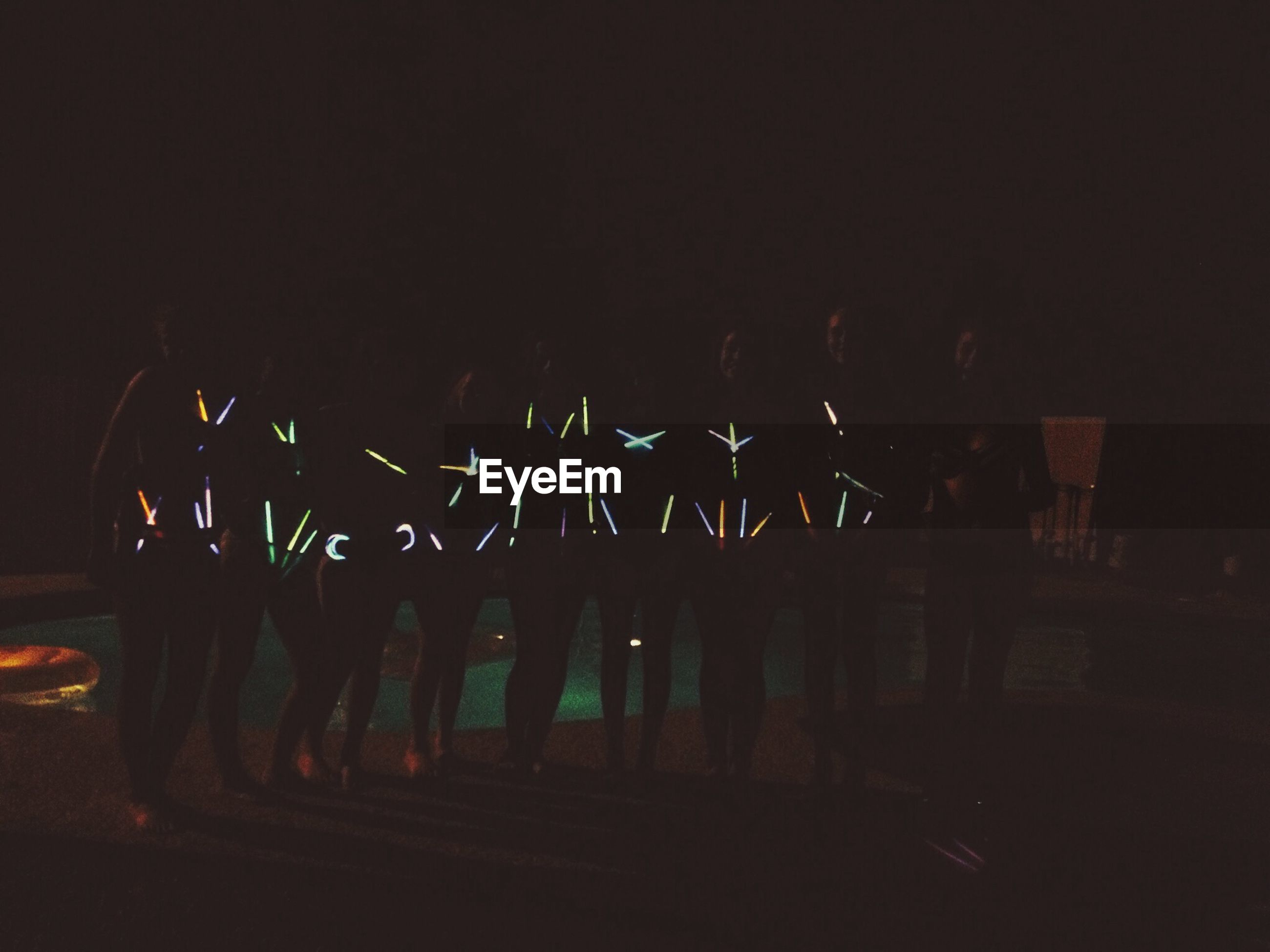 night, illuminated, arts culture and entertainment, men, dark, silhouette, lifestyles, large group of people, leisure activity, copy space, person, glowing, light - natural phenomenon, outdoors, event, fire - natural phenomenon, group of people, motion, standing
