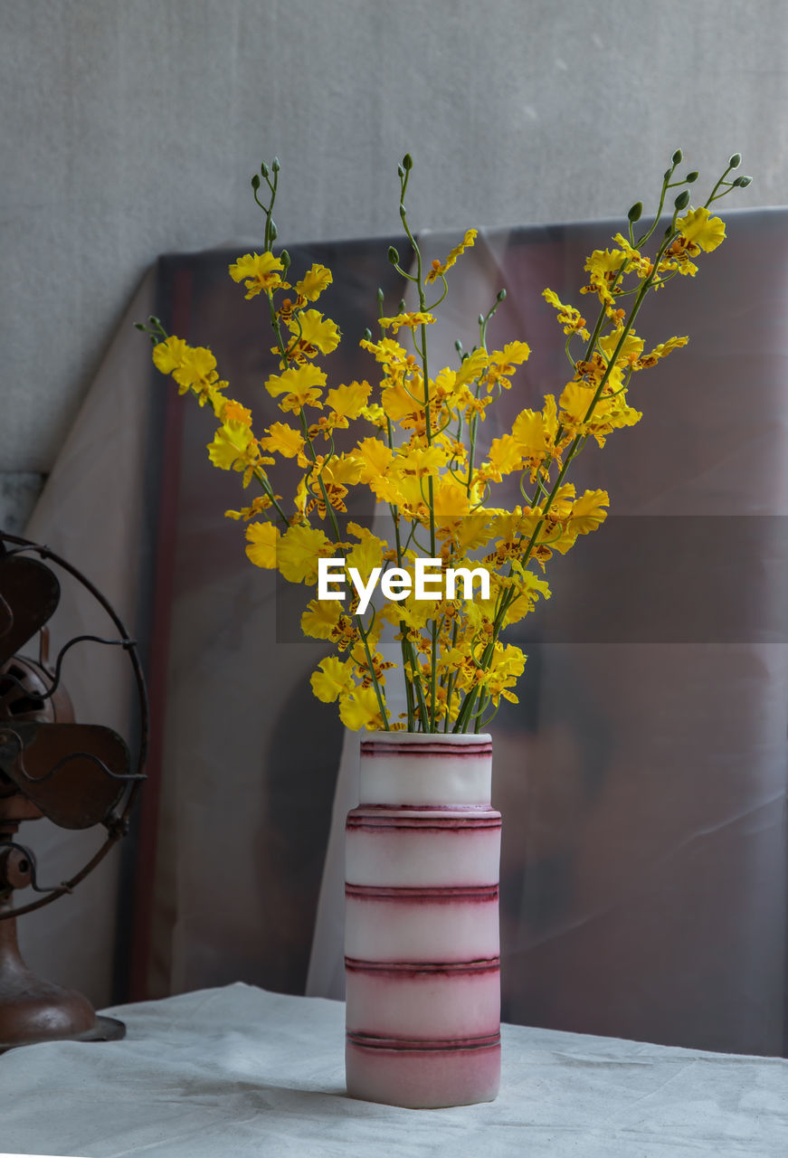 CLOSE-UP OF YELLOW FLOWER VASE ON TABLE AGAINST WALL
