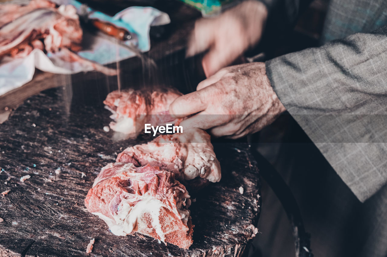 meat, freshness, food, human hand, real people, food and drink, one person, hand, preparation, midsection, raw food, human body part, men, unrecognizable person, selective focus, day, holding, preparing food, occupation, outdoors
