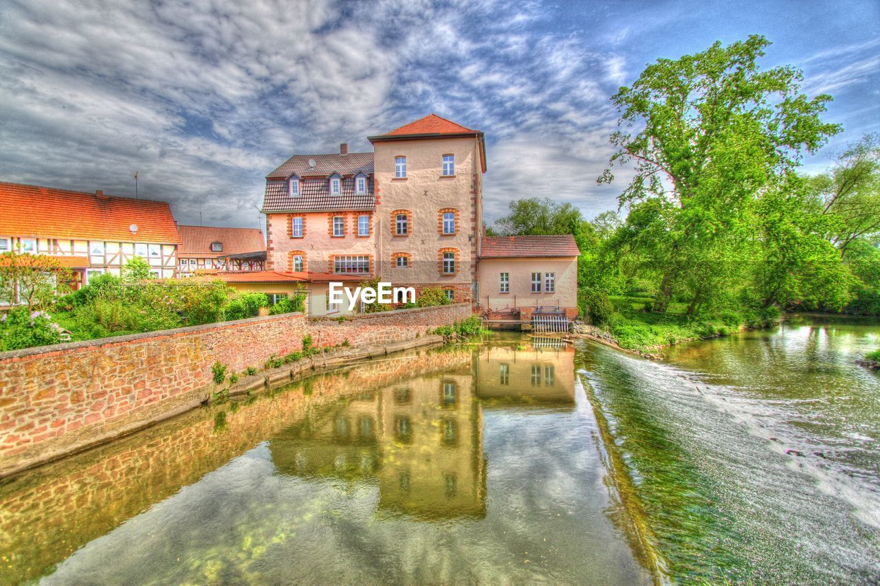 architecture, built structure, building exterior, water, sky, reflection, cloud - sky, tree, outdoors, house, day, waterfront, no people, nature