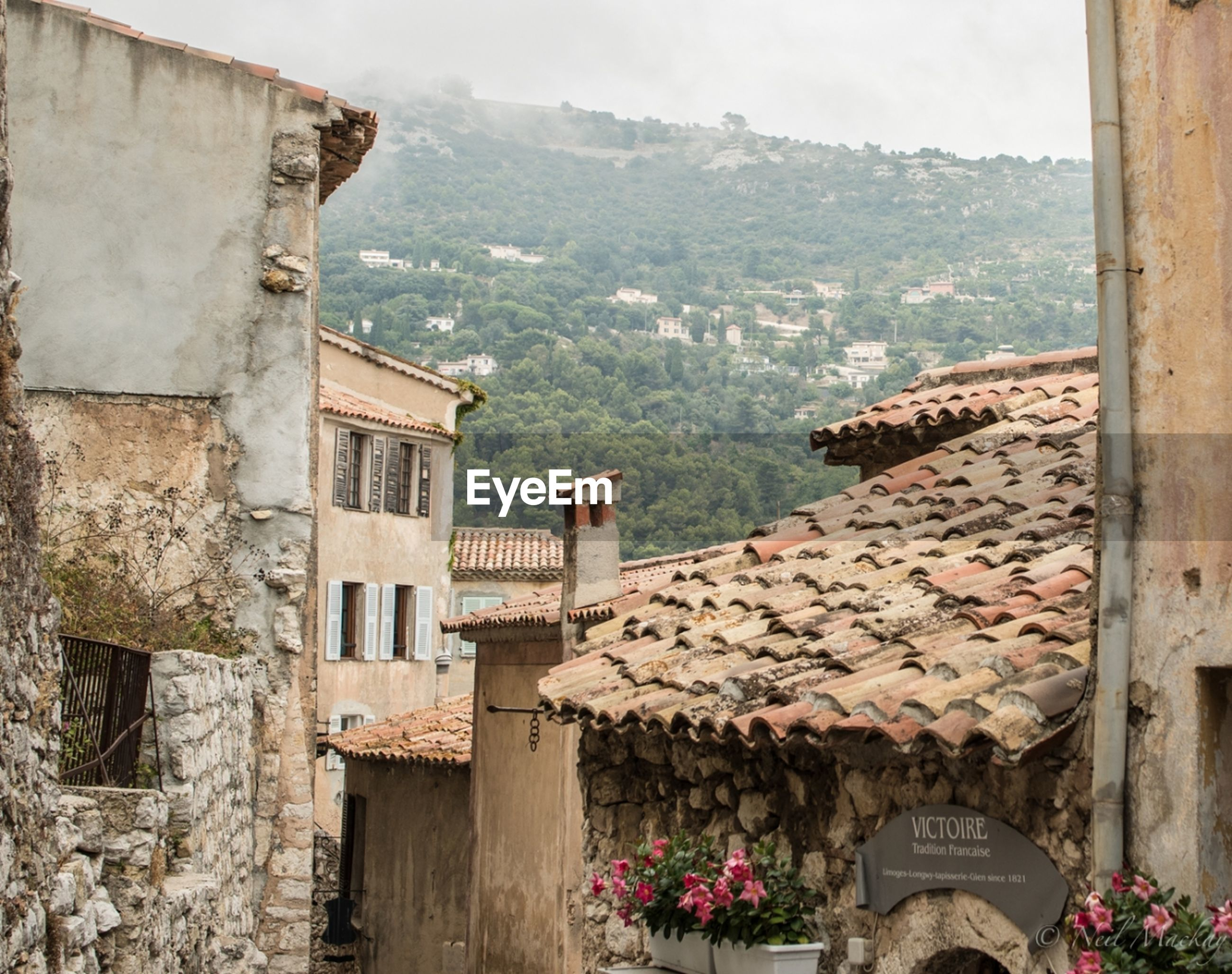 architecture, built structure, window, building exterior, residential building, mountain, town, sea, water, nature, beauty in nature, scenics, outdoors, exterior, rocky mountains, green color, residential district, stone material, history, santorini, tranquil scene, stone
