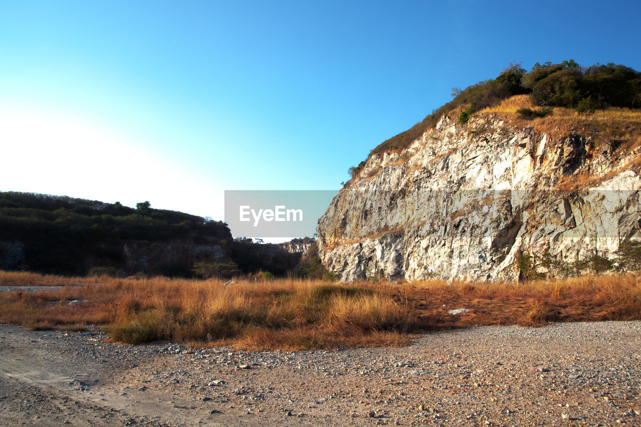rock - object, nature, landscape, tranquility, non-urban scene, clear sky, day, tranquil scene, scenics, no people, outdoors, beauty in nature, mountain, sunlight, road, grass, sky