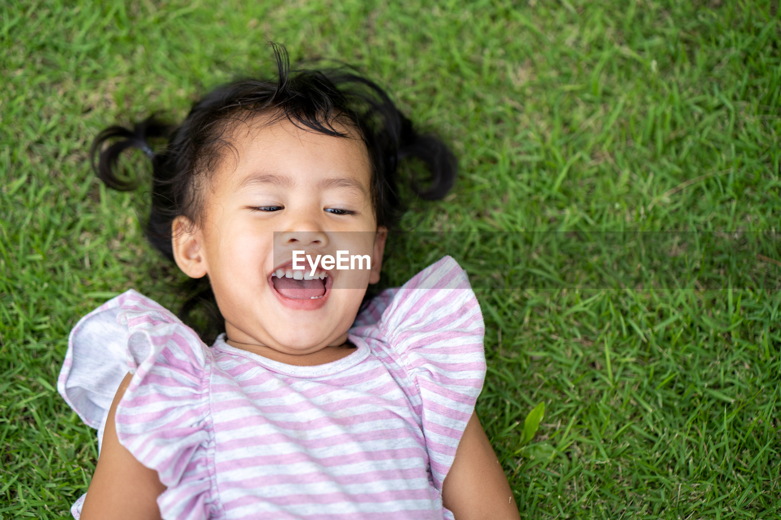 High angle view of cute girl lying on grass