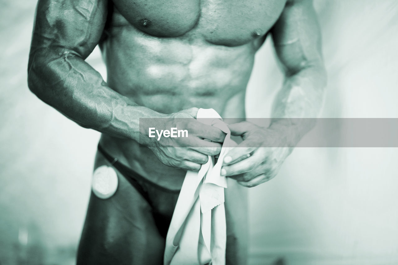 midsection, human body part, lifestyles, one person, men, shirtless, adult, hand, strength, exercising, indoors, muscular build, focus on foreground, body part, vitality, healthy lifestyle, real people, human hand, sport, chest, human muscle, abdominal muscle