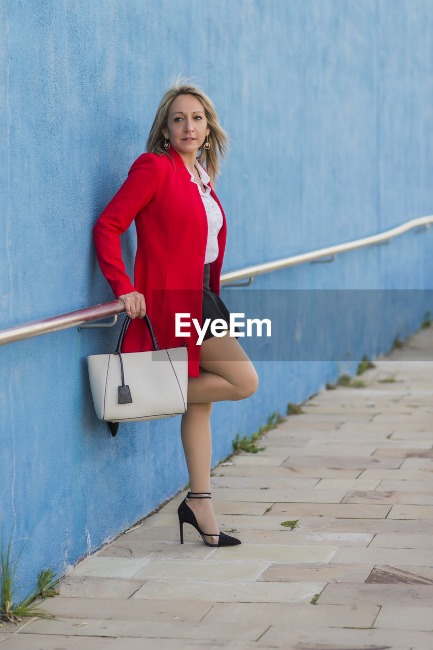 Full length of mature woman holding purse while standing against wall