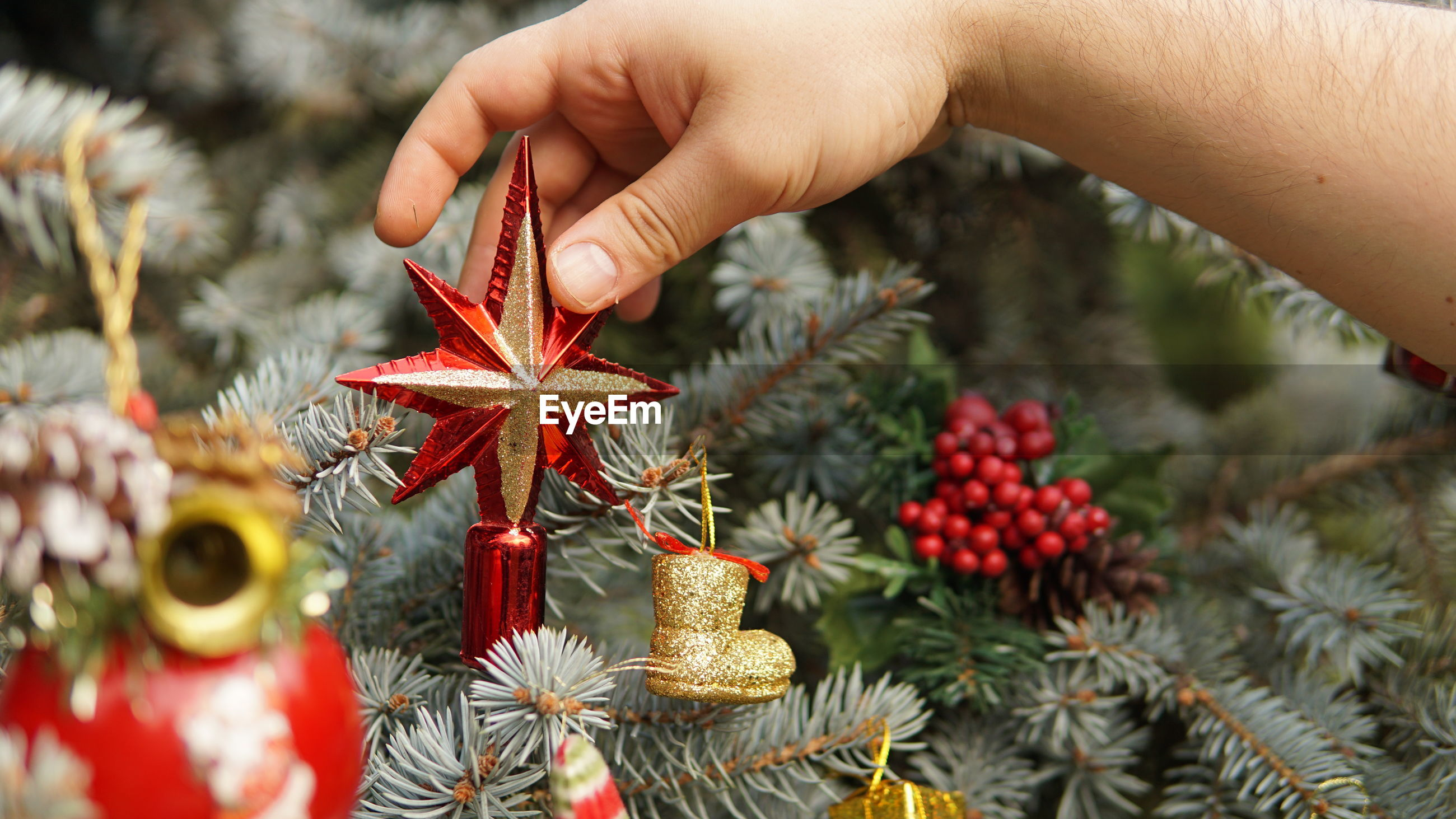 Cropped hand of man decorating christmas tree