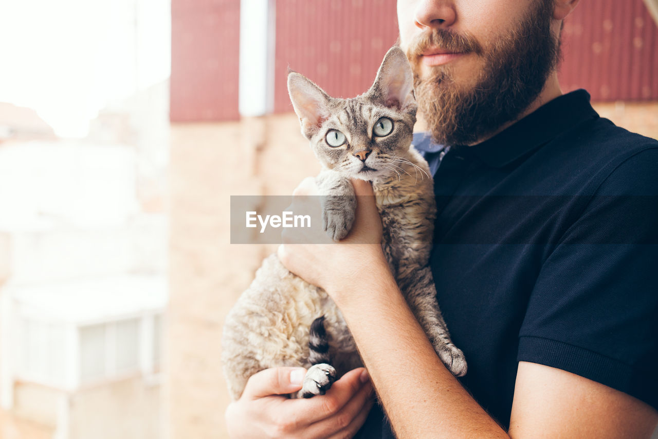 Midsection of man holding cat